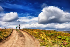 Group people with backpack walking in mountains under dramatic b. Group people with backpack walking on the trail under blue sky Royalty Free Stock Images