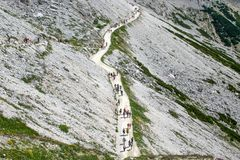 A group of people with backpacks walking along the pathway, Dolomites, Italy. royalty free stock photography