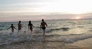 Group Of People On Beach At Sunset Running In Sea Making Splashes Mix Race Cheerful Friends On Vacation stock video footage