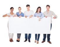 Group of people with billboard. Group Of Happy People Holding White Billboard Over White Background stock photos