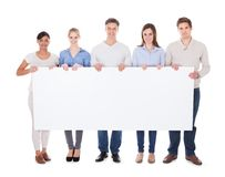 Group Of People With Billboard. Group Of Happy People Holding White Billboard Over White Background royalty free stock photos