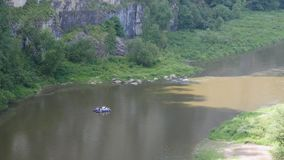 A group of people rafts along the river stock video footage