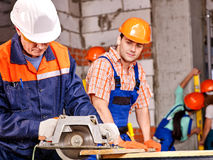 Group people  builder with circular saw Royalty Free Stock Images