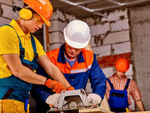 Group people  builder with circular saw . Stock Photography
