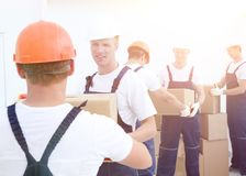 Group of people builders with boxes. Happy male movers in uniform carrying boxes Stock Photo