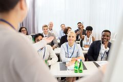 Group of people at business conference or lecture. Business and education concept - businesswoman or lecturer talking to group of people at conference royalty free stock photography