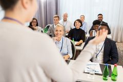 Group of people at business conference or lecture. Business and education concept - businesswoman or lecturer talking to group of people at conference or lecture royalty free stock photos