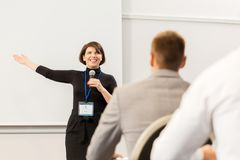 Group of people at business conference or lecture. Business, education and people concept - smiling businesswoman or lecturer with microphone talking to group of stock photography