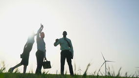 A group of people in business suits gives high five at wind generators background