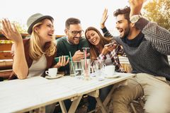 Group of people at cafe talking laughing Royalty Free Stock Images