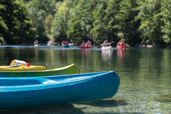 Group of People Canoeing and Kayaking on River in Forest during Summer Holiday during Summer Holiday Royalty Free Stock Images
