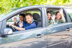 Group of people in the car waving hands. Group of people in the car. They are a multicultural group of friends leaving for a trip. There are two men sitting on Stock Image
