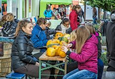 Group of people carving pumpkins on the street, Halloween holida Royalty Free Stock Photography