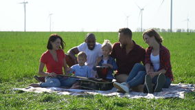 Group of people with children enjoy the wonderful weather at a picnic. Black and white guys with two white girls and two children enjoy the wonderful weather on stock video
