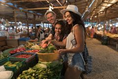 Group Of People Choosing Vegetables On Market Happy Smiling Buy Products Together Young Tourists Shopping Fresh Exotic. Food On Vacation On Asian Bazaar stock image
