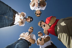 Group Of people In Circle Aiming Guns. Low angle portrait of people aiming guns in circle against sky Stock Photography