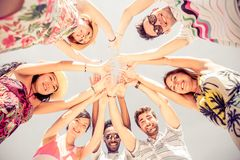 Group of people in circle formation. Group of friends in circle looking down and rising hands - Several people exulting on the beach at sunset - Concepts about Royalty Free Stock Photos