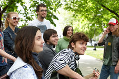 Group of people in city park listen music. Royalty Free Stock Images