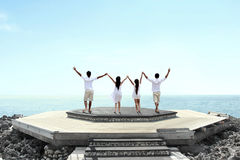 Group of people on cliff raise hands together Stock Image