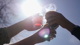 A group of people clinking glasses of beautiful glass with drinks against the sky and sun with a lens effect. HD