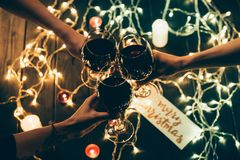 Group of people clinking wineglasses. Cropped shot of four people clinking glasses with red wine over wooden table with fairylights and merry christmas card Royalty Free Stock Image