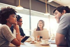 Group of people at coffee shop for startup meeting. Portrait of group of young people sitting at a cafe and discussing work. Young men and women at coffee shop Royalty Free Stock Photography