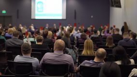 A group of people at a conference vote raising raising cards of red and green color. view from the back of the hall with stock video footage