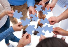 Group of people connecting puzzle pieces. High angle view of people connecting puzzle pieces over white background royalty free stock image