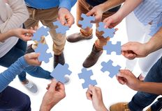Group of people connecting puzzle pieces. High angle view of people connecting puzzle pieces over white background royalty free stock photography