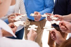 Group of people connecting puzzle pieces. High angle view of people connecting puzzle pieces over white background stock photo