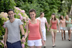 Group of people with couples walking outdoors. On a beautiful spring or summer day stock photo