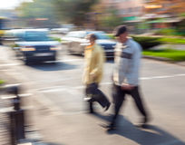 Group of people crossing the street at a crosswalk Stock Image