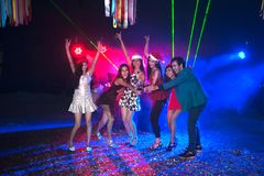 Group of people dancing at night club party and lights background. Group of people dancing at night club with Santa hat Christmas holidays party friendship Royalty Free Stock Photography