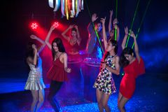 Group of people dancing at night club party and lights background. Group of people dancing at night club with Santa hat Christmas holidays party friendship Stock Photo