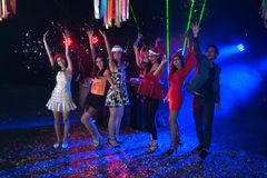 Group of people dancing at night club party and lights background. Group of people dancing at night club with Santa hat Christmas holidays party friendship Royalty Free Stock Image
