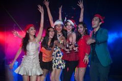 Group of people dancing at night club party and lights background. Group of people dancing at night club with Santa hat Christmas holidays party friendship Royalty Free Stock Photo