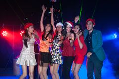 Group of people dancing at night club party and lights background. Group of people dancing at night club with Santa hat Christmas holidays party friendship Stock Photos