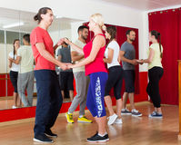 Group of people dancing salsa in studio Stock Image