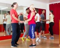 Group of people dancing salsa in studio Stock Image