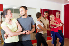 Group of people dancing salsa in studio. Group of smiling european people dancing salsa in studio Stock Photography