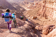 Group people descending walking stone desert trail backpacking travel. Group backpackers people traveling descending desert trail stone cliffs, hiking mountains royalty free stock photography
