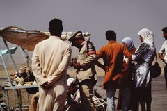 Group of People on Desert Beside Brown Tent Stock Photo