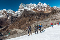 Group of People of different Age crossing Glacier in high Mountains Royalty Free Stock Images