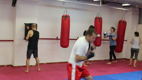 Group of people of different ages training in the boxing hall. Men and women of different ages practicing boxing punches stock footage
