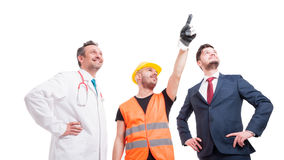 Group of people with different occupations. Low angle shot of group of people with different professional occupations indicate something on white background Stock Images