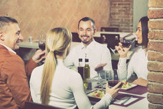 Group of people dining out merrily in country restaurant. Group of  cheerful  people dining out merrily in country restaurant Royalty Free Stock Photo