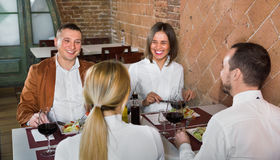 Group of people dining out merrily in country restaurant. Group of smiling people dining out merrily in country restaurant Stock Photo