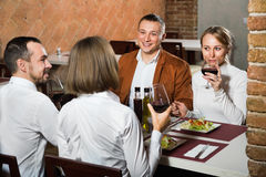 Group of people dining out merrily in country restaurant. Group of smiling  friendly people dining out merrily in country restaurant Stock Photo