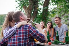 Group Of People Dining Togetherness Concept. Best friends are drinking tasty beer on a summer picnic. Royalty Free Stock Photo