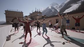 Group of people do yoga at outdoor playground in sunny morning, raise hands. Snowy mountains. Trainer. Concentration stock video footage